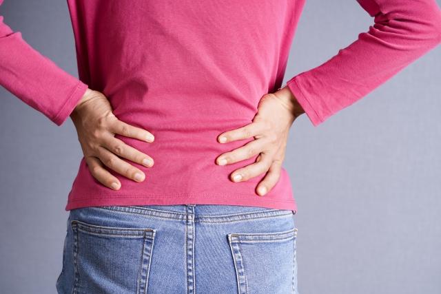 腰痛で腰を押さえる女性