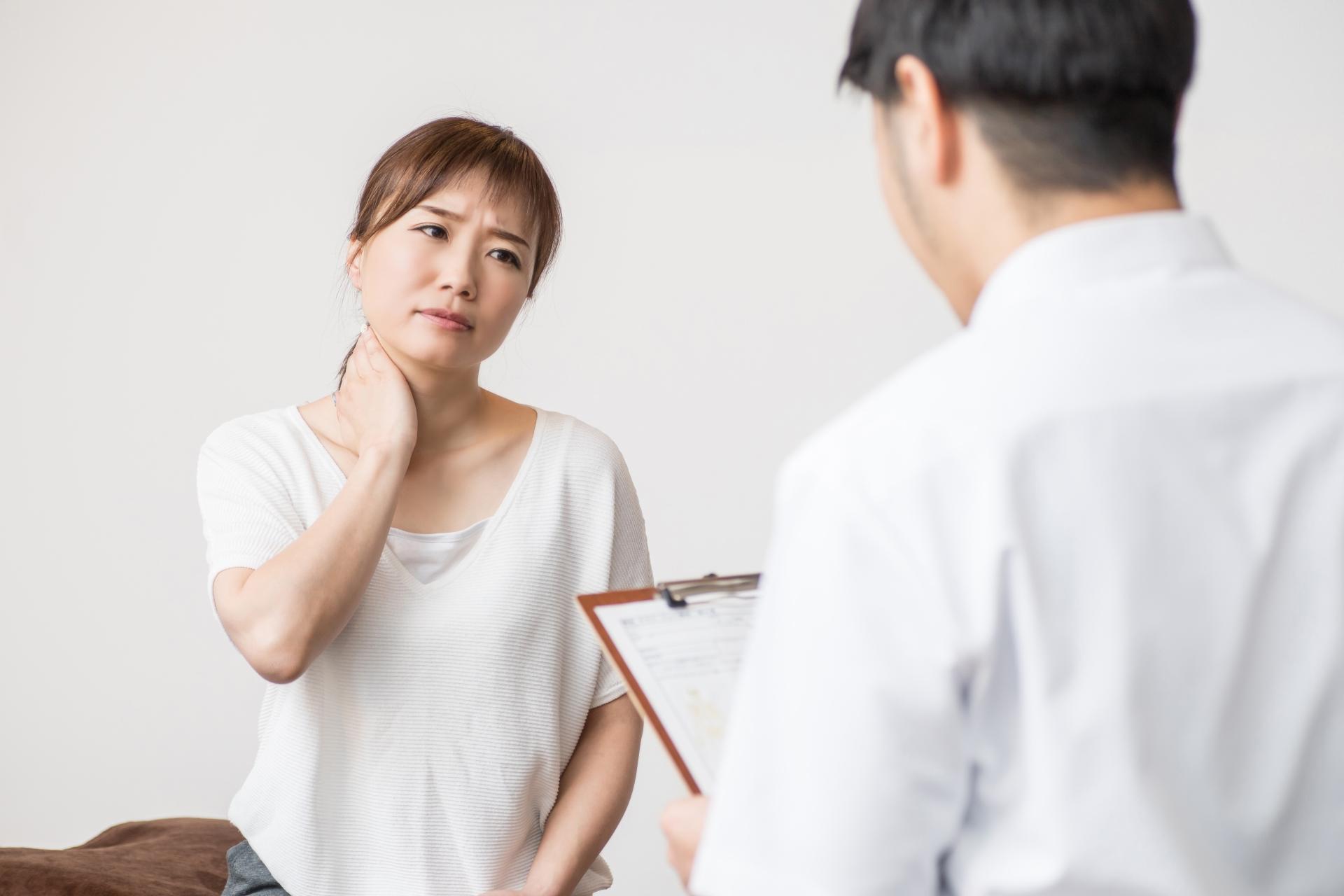首の痛みを相談する女性